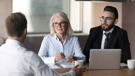 Diverses équipes de recruteurs multiethniques écoutent les candidats masculins parler en partageant leurs réflexions lors de l'entretien, les employeurs multiraciaux ou les chasseurs de têtes considèrent le candidat à l'embauche, concept de recrutement Banque d'images