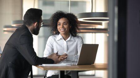 Smiling african American woman employee talk with male colleague discuss business project on laptop together, multiethnic diverse colleagues or partners consider cooperation at meeting in office