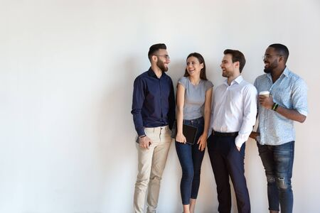 Happy mixed race four employees managers workers standing near wall, having fun. Successful multiethnic business team members corporate staff laughing, enjoying relaxed working atmosphere together. Stock Photo