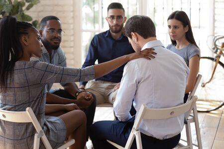 Compasiva empleada afroamericana poniendo la mano sobre el hombro de compañeros de trabajo desesperados, apoyando, expresando condolencias. Equipo diverso de trabajadores de raza mixta sentados en círculo en terapia de grupo.