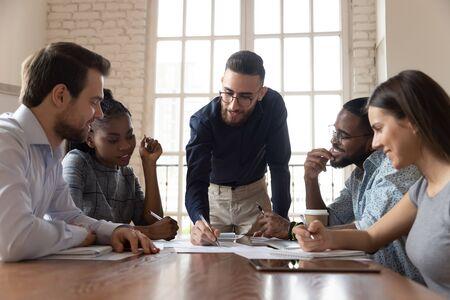 Un jeune chef d'équipe masculin arabe motivé et engagé se penche sur une table, discute d'idées de projet avec l'équipe de partenaires de race mixte impliquée, dessine des graphiques sur papier, explique son opinion personnelle au bureau.
