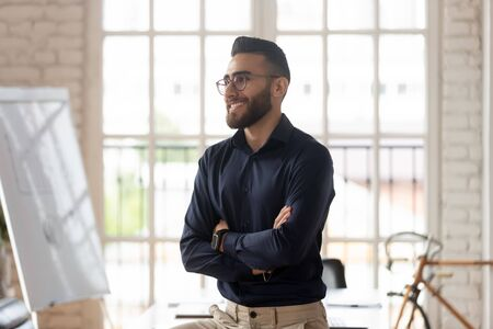 Half side view young confident middle eastern ethnicity pleasant businessman standing with folded hands at creative working place, thinking of career opportunities, planning company growth strategies.