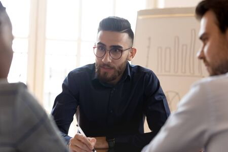 Engaged confident middle eastern ethnicity young businessman listening to multiracial partners or clients at office, head shot. Motivated arabic job applicant holding interview with hr managers.