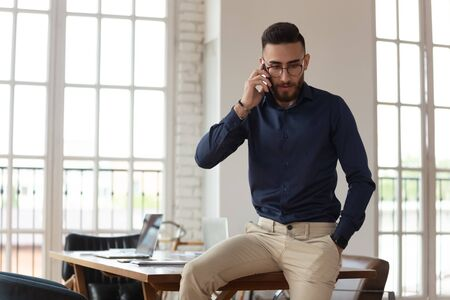 Worried millennial arabic male employee sitting on table, talking on cellular phone, listening to client complaints. Young middle eastern ethnicity businessman helping solving problems, consulting.