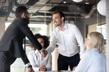 Smiling young businessmen handshake greeting or get acquainted at office meeting, happy male colleagues or business partners shake hands closing deal or congratulating with success at briefing