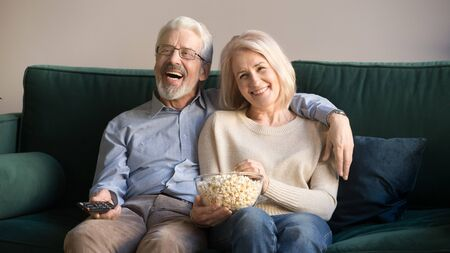 Happy elderly couple in love sit on couch wife hold pop-corn bowl husband remote control aged family enjoy weekend watching comedy tv show movie laughing, activities of retired people at home concept