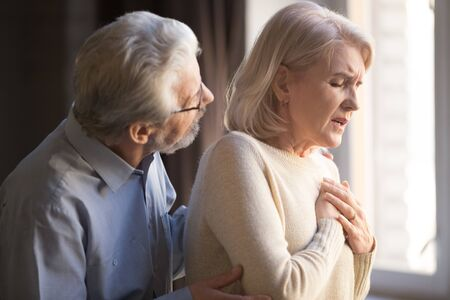 Close up focus on elderly wife hold hand on breast touch chest having heart attack feels unwell, worried husband supporting her, myocardial infarction symptoms, immediately emergency call need concept Stock Photo