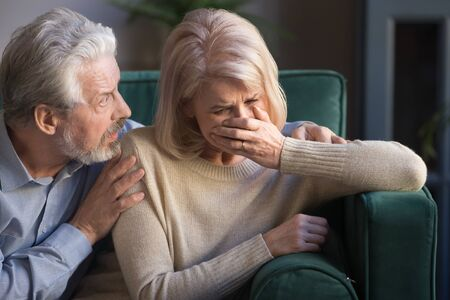 Elderly spouses sit on sofa at home, desperate wife crying worried anxious husband embrace her comforting beloved woman, sad life event, senile disease diagnosis, psychological mental problems concept Imagens