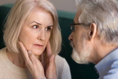 Elderly couple grey-haired husband touches strokes face of beloved blond wife close up image, moment of caress, man showing empathy care love, unhealthy woman sharing anxieties with loving man concept