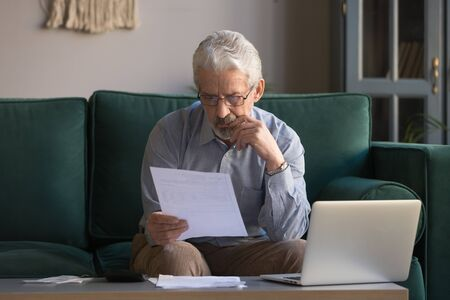 Serious mature man wearing glasses sitting on couch in living room manage budget received invoice analyzes month expenses feels concerned about public utility debt, check read loan documents concept Stock fotó