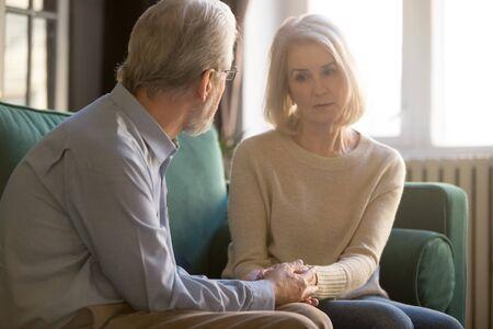 Sechzig Jahre alte Ehepartner, die auf der Couch sitzen, liebevoller älterer Ehemann, der traurige frustrierte Frau tröstet, grauhaariges Paar hält Hände Mann zeigt Liebe, Fürsorge und Empathie und zeigt das Konzept der Unterstützung der geliebten Frau Standard-Bild