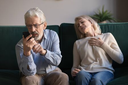 Sixty years old man holds phone makes emergency call calling 911 while his elderly wife leaning on couch put hand on chest feeling unwell lightheadedness, shortness of breath, concept of heart attack