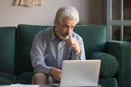 Mature businessman take off glasses look at pc screen feel astonished sitting on couch at home, senior man read shocking online news, worried old male confused by bad email or computer problem concept