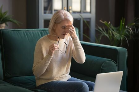 Overworked aged blond woman sitting on sofa in living room take off glasses suffers from dry eyes, eye strain problem, blurry vision after long usage and working on computer electronic devices concept