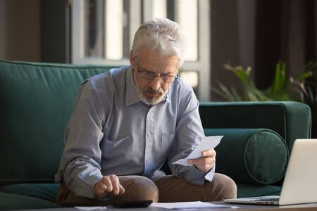 Sixty years old retiree man sit on couch holding receipt paper calculates on calculator monthly expenses, elderly male managing budget, planning finances, analyzes charges, check utility bills concept