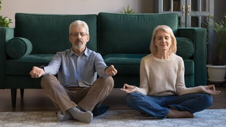Spouses sitting in lotus pose on warm floor in living room, sixty years serene wife husband meditating do breath exercises feels calmness and serenity, yoga time, healthy lifestyle of retirees concept