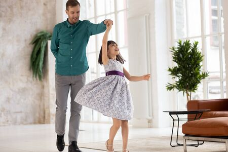 Happy young dad dance swirl cute little daughter in beautiful princess dress at home, loving father have fun with excited preschooler girl child, engaged in funny activity, swaying in living room Stock Photo