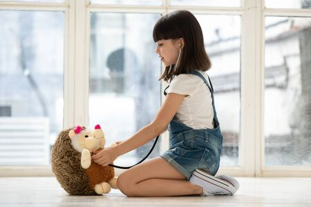 Cute little girl sit on warm home floor play doctor patient game listen with stethoscope to fluffy hedgehog heart, small kid future nurse involved in childish activity take care of stuffed toy