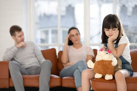 Upset little preschooler girl feel lonely hug stuffed toy friend suffer from parents fight or quarrel, sad small child having psychological problems stressed affected by divorce, family problems Stockfoto