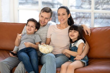 Smiling young family with preschooler children sit relax on sofa watching movie on tv eating popcorn, happy parents rest at home with little kids enjoy weekend together, have fun in living room 版權商用圖片
