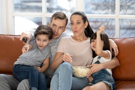 Young parents sit on couch relax with cute little kids watching movie or cartoon on tv together, mom and dad rest at home enjoy video eating popcorn with preschooler children, family weekend concept