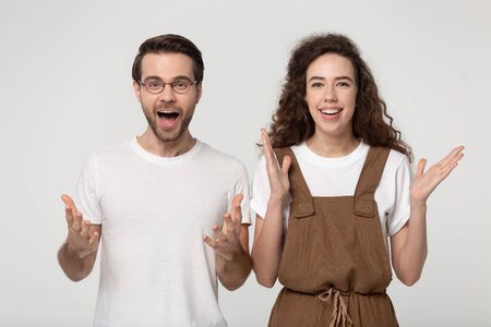 Overjoyed millennial couple stand isolated on grey studio background look at camera feel stunned astonished with good sale offer, amazed man and woman smile surprised by promotion or deal