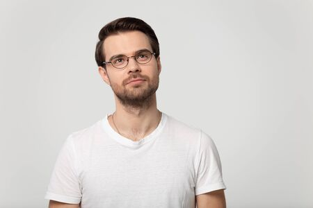 Pensive millennial Caucasian man wearing glasses and white t-shirt isolated on grey studio background look up thinking, thoughtful male in spectacles feel pensive considering sale offer or deal Banco de Imagens