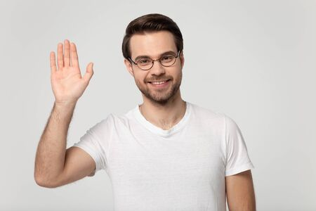 Smiling Caucasian millennial man in glasses and white t-shirt isolated on grey studio background look at camera greeting, happy male blogger in spectacles wave hand say hello to audience, subscribers Фото со стока - 138013374