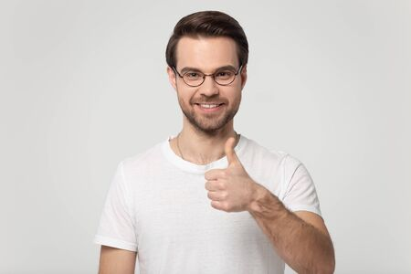 Happy Caucasian young man in glasses and white t-shirt isolated on grey studio background show thumbs up give recommendation, smiling male in spectacles look at camera recommend good service or deal