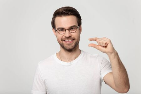 Happy Caucasian guy wearing glasses and white t-shirt isolated on grey studio background look at camera show small prices, smiling man in spectacles demonstrate little measurement or amount by hands Imagens