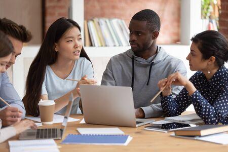 Centrado joven india y chico negro escuchando groupmate. Estudiante asiática explicando los detalles del proyecto escolar o compartiendo ideas con amigos de la universidad. Grupo de diversos adolescentes trabajando juntos.