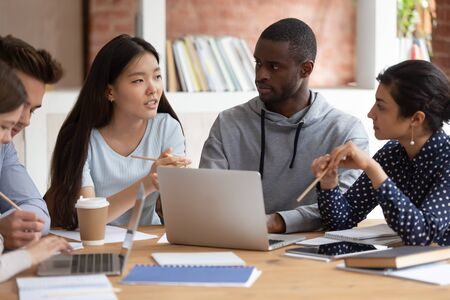 Koncentruje się młoda indyjska dziewczyna i czarny facet słuchając kolegi z grupy. Azjatycka studentka wyjaśniająca szczegóły szkolnego projektu lub dzieląca się pomysłami z przyjaciółmi ze studiów. Grupa różnorodnych nastolatków pracujących razem.