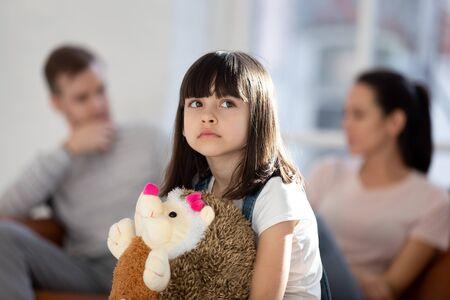 Verdrietig meisje voelt zich overstuur eenzaam knuffel pluizig speelgoed egelvriend getroffen door oudergevecht of ruzie, overstuur klein kind eenling gestrest met moeder en vader echtscheiding of splitsing, familieproblemen concept