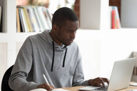 Serious concentrated african american male student using laptop, busy with studying, preparing for evaluation examination, final test or session. Motivated black guy doing homework or writing essay.