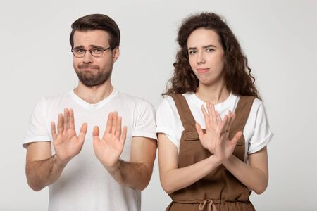 Displeased millennial couple isolated on grey studio background look at camera denying bad sale offer, dissatisfied unhappy man and woman make gesture say no reject refuse proposal or suggestion