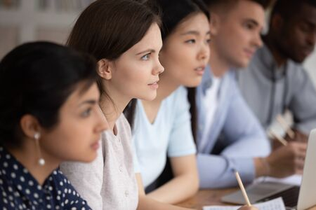 Focused group of mixed race students sitting together at lecture, carefully listening to teacher or trainer at college. Concentrated attentive diverse teammates listening to material explanation.