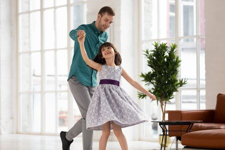 Excited young father and cute little preschooler daughter wearing beautiful princess dress have fun swaying in living room, happy dad and small girl child dancing swirling at home, relaxing together Reklamní fotografie