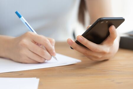 Close up view young woman holding smartphone, scrolling or searching information on device, writing down notes on paper. Concentrated female student getting ready for exams or test, browsing data.