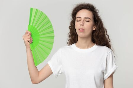 Unhappy millennial girl isolated on grey studio background hold waving with green hand fan save from hot weather, overheated young female use waver suffering from heat, feeling sick uncomfortable Stockfoto