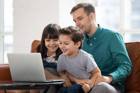 Excited small preschooler boy and girl kids have fun watching cartoon on laptop with young caring dad, loving father relax spend time with little children using computer, play game online or learning