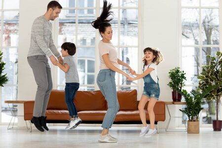 Playful young family with preschooler kids have fun engaged in funny activity at home, excited smiling parents and cute small children jumping in modern light living room, enjoy day off together Imagens