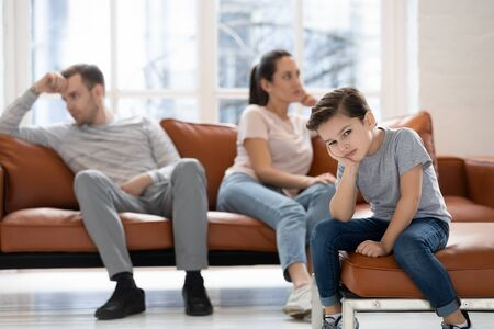 Sad small boy child sit alone stressed witnessing parents fight or quarrel suffer from domestic violence situation, upset little kid feel depressed affected by mom and dad dispute breakup or divorce Stockfoto
