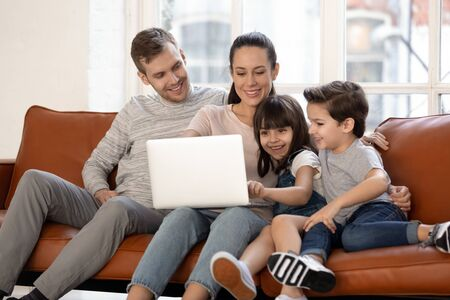 Happy young family with cute preschooler kids have fun at home watching movie on laptop together, loving parents and little children relax in living room smile enjoying cartoon on computer Stockfoto