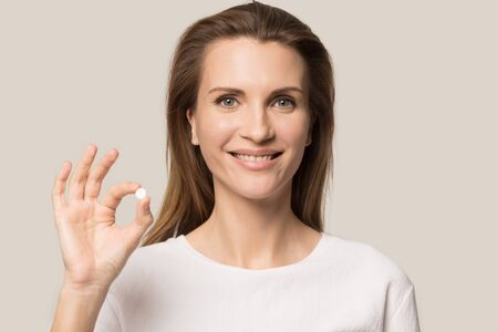 Head shot attractive woman showing white round tablet, medicine, healthcare concept, satisfied female, client looking at camera, holding small pill in hand, isolated on studio background