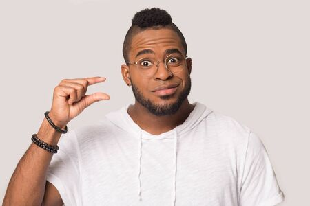 Funny positive African American man in glasses showing small size by fingers, gesture, looking at camera, young male demonstrate tiny measure, low price, isolated on studio background