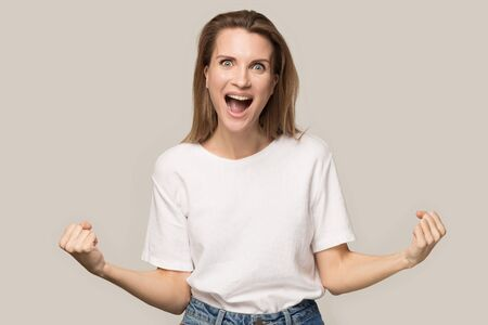 Excited woman celebrating win, satisfied by good result, screaming with joy, attractive lucky female winner motivated by achievement, successful deal, look at camera, isolated on studio background