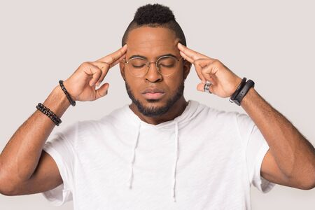 Nervous African American man touching temples, relieving headache, breathing, exhausted male calming down, suffering from pain, migraine, meditating, isolated on studio background