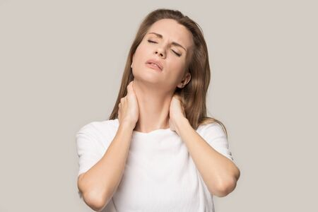 Tired upset woman with closed eyes massaging tensed neck muscles, stress relief, exhausted student or businesswoman suffering from pain, feeling physics discomfort, isolated on grey studio background