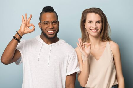 Happy African American man in glasses and woman with wide toothy smile showing ok sign, all right gesture, satisfied clients recommend service, looking at camera, isolated on studio background