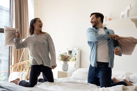 Happy playful young adult romantic couple playing pillow fight on bed together, cheerful carefree man and woman having fun laughing in bedroom interior in morning enjoy lifestyle game at home hotel Foto de archivo - 134572409